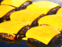 row of hamburger patties cooking on the grill with cheese