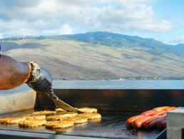 chef working the grill making hamburgers with ocean and maui island in the background