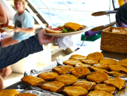 grill with rows of burgers being prepared for the guests aboard the pride of maui boat afternoon tour